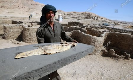 An Egyptian workers carries artefacts which are part archeological discovery named the 'Lost Golden City' in Luxor, Egypt,  10 April 2021. Egyptian archaeologists have discovered a 3,000 years old city in Luxor. A mission under Dr. Zahi Hawass found the remains in excavation works that started in September 2020. The scientists believe the find dates back to the reign of Amenhotep III, and is thought to be used afterwards by Tutankhamun and Ay.