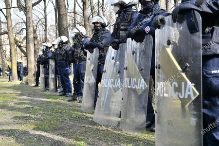Polish riot police officers cordon off the members and supporters of informal civic movement Citizens of Poland during their protest against the ceremonies commemorating the 11th anniversary of the presidential plane crash near Smolensk, near on Pilsudski Square in Warsaw, Poland, 10 April 2021. Poland's President Lech Kaczynski, his wife Maria Kaczynska and 94 others died on 10 April 2010 when Polish plane crashed in Smolensk, Russia.