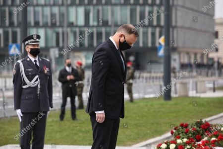 Polish President Andrzej Duda (C) lays a candle at the Monument to former Polish President Lech Kaczynski on Pilsudski Square during the ceremonies commemorating the 11th anniversary of the presidential plane crash near Smolensk, in Warsaw, Poland, 10 April 2021. Poland's President Lech Kaczynski, his wife Maria Kaczynska and 94 others died on 10 April 2010 when Polish plane crashed in Smolensk, Russia.
