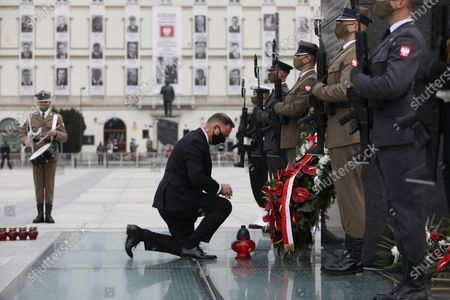 Polish President Andrzej Duda (C) lays a candle at the Monument to the Victims of the Smolensk plane crash at Pilsudski Square during the ceremonies commemorating the 11th anniversary of the presidential plane crash near Smolensk, in Warsaw, Poland, 10 April 2021. Poland's President Lech Kaczynski, his wife Maria Kaczynska and 94 others died on 10 April 2010 when Polish plane crashed in Smolensk, Russia.