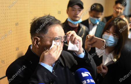 Stock Picture of (210409) - WUHAN, April 9, 2021 (Xinhua) - Zhang Boli (1st L), an academician of the Chinese Academy of Engineering and head of Tianjin University of Traditional Chinese Medicine, wipes tears during his visit at the makeshift hospital in Jiangxia District in Wuhan, central China's Hubei Province, April 9, 2021. Featuring traditional Chinese medicine treatment, the makeshift hospital in Wuhan's Jiangxia District was transformed from a sports center. It received a total of 564 patients till its closure on March 10, 2020. None of them saw their health condition slash.