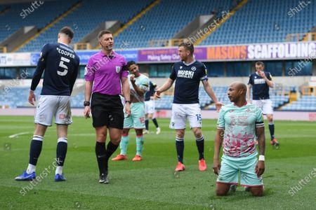 Referee Robert Jones tells Andre Ayew of Swansea City to get up