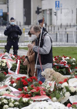 People gesture after laying flowers by the monument of the late President Lech Kaczynski on the anniversary of the plane crash which killed him and 95 other people in 2010, following state ceremonies in downtown Warsaw, Poland