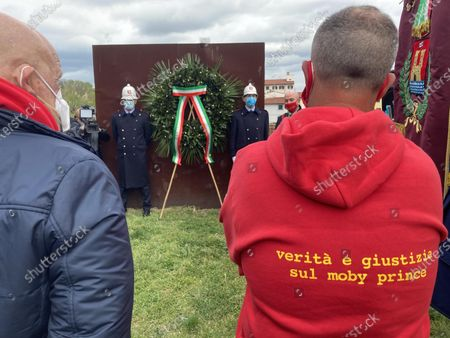 Stock Picture of A wreath is placed in front of a monument in memory of the victims of the Moby Prince ship, on occasion of the 30th year since the tragedy in Livorno, Italy, 10 April 2021. The ceremony was attended by civil and military authorities and the relatives of the victims. The Moby Prince ferry collided with a tanker and caught fire in the port of Livorno leaving 140 passengers and crew members dead on 10 April 1991. The sentence on the sweater reads: truth and justice about moby prince.