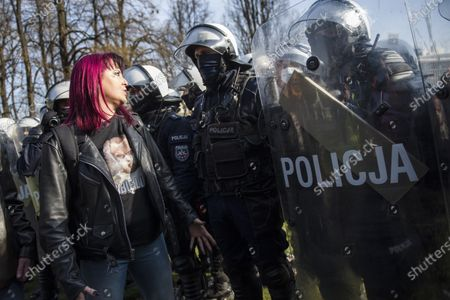 A protester confronts anti-riot policemen during the anniversary. Poland has commemorated the 11th anniversary of a plane crash near the Russian city of Smolensk that killed 96 people including Poland's then-President Lech Kaczynski, his wife, and many of the country's senior political and military officials. Hundreds of anti-riot policemen were protecting the event, numerous opponents protesting against the government and lockdown restrictions were detained.