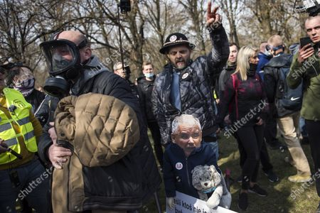 A protester makes a gesture while holding a puppet of Jaroslaw Kaczynski during the anniversary. Poland has commemorated the 11th anniversary of a plane crash near the Russian city of Smolensk that killed 96 people including Poland's then-President Lech Kaczynski, his wife, and many of the country's senior political and military officials. Hundreds of anti-riot policemen were protecting the event, numerous opponents protesting against the government and lockdown restrictions were detained.