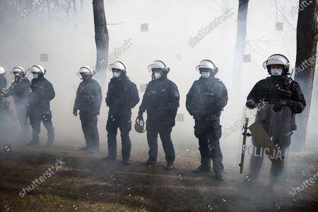 Anti-riot policemen stand on guard amid teargas smoke during the anniversary. Poland has commemorated the 11th anniversary of a plane crash near the Russian city of Smolensk that killed 96 people including Poland's then-President Lech Kaczynski, his wife, and many of the country's senior political and military officials. Hundreds of anti-riot policemen were protecting the event, numerous opponents protesting against the government and lockdown restrictions were detained.