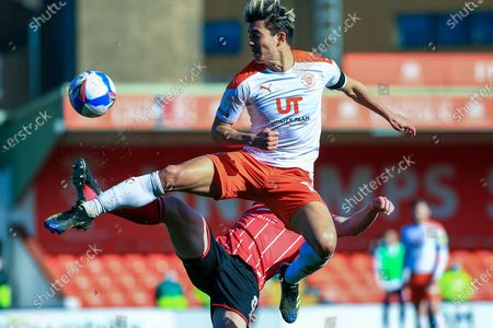 Kenny Dougall (12) of Blackpool is tackled by James Jones (8) of Lincoln City during the EFL Sky Bet League 1 match between Lincoln City and Blackpool at Sincil Bank, Lincoln