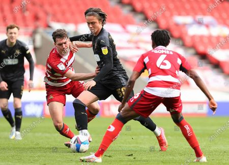 Wigan Athletic midfielder Thelo Aasgaard (30)dribbles the ball between Doncaster defender Joe Wright (5)and Doncaster midfielder Madger Gomes (6) during the EFL Sky Bet League 1 match between Doncaster Rovers and Wigan Athletic at the Keepmoat Stadium, Doncaster