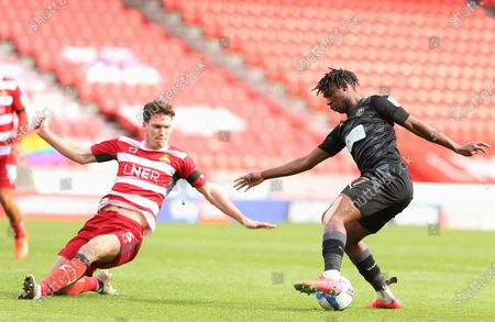 Wigan Athletic midfielder Viv Solomon-Otabor (17) takes on Doncaster defender Joe Wright (5) during the EFL Sky Bet League 1 match between Doncaster Rovers and Wigan Athletic at the Keepmoat Stadium, Doncaster
