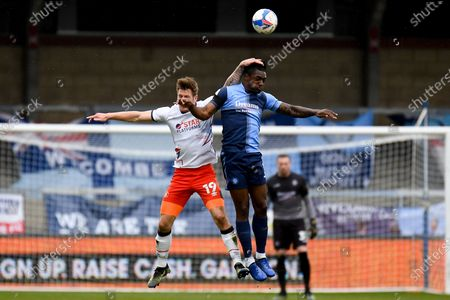 Stock Image of Wycombe Wanderers defender Anthony Stewart (5) heads the ball  under pressure from Luton Town forward James Collins (19) during the EFL Sky Bet Championship match between Wycombe Wanderers and Luton Town at Adams Park, High Wycombe
