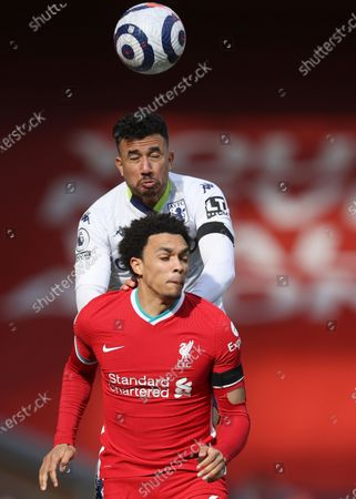 Aston Villa's Trezeguet, atop, and Liverpool's Trent Alexander-Arnold challenge for the ball during the English Premier League soccer match between Liverpool and Aston Villa at Anfield stadium in Liverpool, England