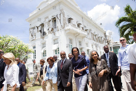 First Lady Michelle Obama and Dr. Jill Biden tour earthquake damage in Port Au Prince, Haiti, along with Haitian President Rene Preval, and Elisabeth Delatour Preval, the First Lady of Haiti. The damaged presidential palace is seen in the background.