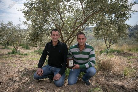 """(210410) - MESSINIA, April 10, 2021 (Xinhua) - Photo taken on April 1, 2021 olive growers Stavros (L) and Constantinos Pavlopoulos posing with a jar of their own Kalamata olives in their family's olive grove in Messinia, Greece. Known as the """"black queen"""" of all Greek olives, the Kalamata, grown in the sun-kissed olive groves around Messinia in the southwestern part of the Peloponnese and named after the capital city of the region, has been an integral part of the local gastronomy and economy for centuries.     TO GO WITH """"Feature: Producers of Greece's Kalamata olives seek to conquer China as next big market"""""""