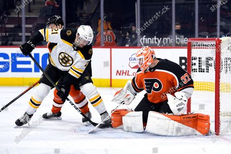 Philadelphia Flyers goaltender Brian Elliott, right, makes a save on a shot attempt by Boston Bruins' Nick Ritchie as Flyers' Robert Hagg, rear, defends during the second period of an NHL hockey game, in Philadelphia