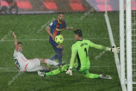 Stock Picture of Barcelona's Jordi Alba, center, challenges Real Madrid's goalkeeper Thibaut Courtois, right, and Alvaro Odriozola during the Spanish La Liga soccer match between Real Madrid and FC Barcelona at the Alfredo di Stefano stadium in Madrid, Spain
