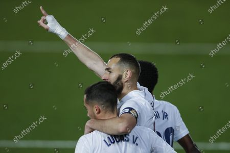 Real Madrid's Karim Benzema, right, celebrates with teammate Lucas Vazquez after scoring the opening goal during the Spanish La Liga soccer match between Real Madrid and FC Barcelona at the Alfredo di Stefano stadium in Madrid, Spain