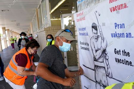 Wilson Perez of the Coalition of Immokalee Workers (CIW) hangs a sign advocating for the COVID-19 vaccine at a clinic held by Healthcare Network, in Immokalee, Fla. The clinic is offering the the Johnson and Johnson COVID-19 vaccine, and is focusing on inoculating migrant farmworkers and their families. Healthcare Network is working with the Coalition of Immokalee Workers (CIW) to vaccinate this vulnerable population