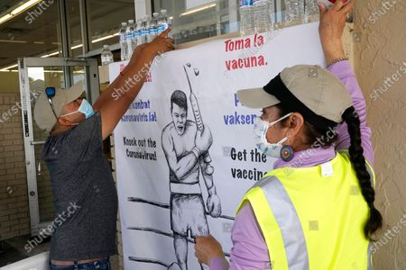 Stock Picture of Wilson Perez, left, and Nely Rodriguez, right, of the Coalition of Immokalee Workers (CIW) hang a sign advocating for the COVID-19 vaccine at a clinic held by Healthcare Network, in Immokalee, Fla. The clinic is offering the the Johnson & Johnson COVID-19 vaccine, and is focusing on inoculating migrant farmworkers and their families. Healthcare Network is working with the Coalition of Immokalee Workers (CIW) to vaccinate this vulnerable population