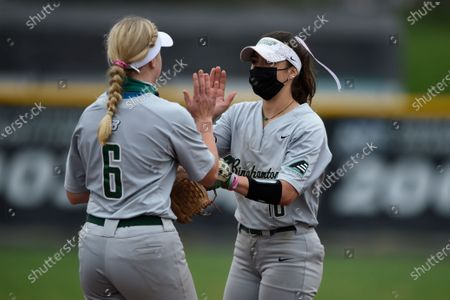 Binghamton's Hannah Lyons, left, and Rayn Gibson during an NCAA softball game, in Baltimore, Md