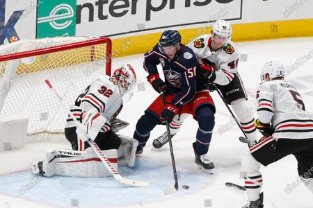 Columbus Blue Jackets' Eric Robinson, center, tries to get a shot off between Chicago Blackhawks' Kevin Lankinen, left, and Wyatt Kalynuk during the third period of an NHL hockey game, in Columbus, Ohio