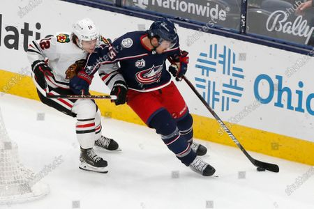 Columbus Blue Jackets' Michael Del Zotto, right, tries to skate past Chicago Blackhawks' Alex DeBrincat during the third period of an NHL hockey game, in Columbus, Ohio