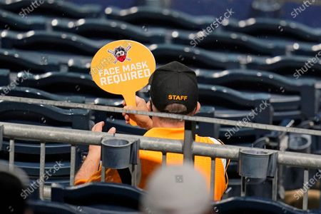 An usher holds a sign reminding the limited number of baseball fans attending a baseball game between the Pittsburgh Pirates and the Chicago Cubs at PNC Park in Pittsburgh, that COVID-19 protocol of mask wearing and social distancing is required