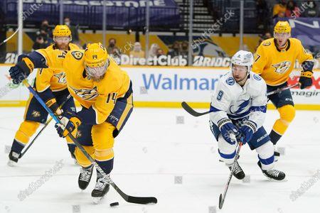 Nashville Predators defenseman Mattias Ekholm (14) and Tampa Bay Lightning center Tyler Johnson (9) battle for the puck in the first period of an NHL hockey game, in Nashville, Tenn