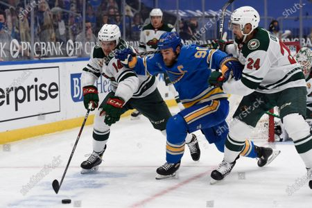 Minnesota Wild's Joel Eriksson Ek (14) and Matt Dumba (24) battle St. Louis Blues' Ryan O'Reilly (90) for the puck during the second period of an NHL hockey game, in St. Louis