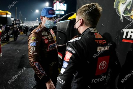 Kyle Busch, left, talks with Christopher Bell during a rain delay at the NASCAR Cup Series auto race at Martinsville Speedway in Martinsville, Va