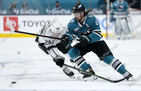 San Jose Sharks defenseman Erik Karlsson (65) moves the puck past Los Angeles Kings center Jaret Anderson-Dolan (28) during the third period of an NHL hockey game, in San Jose, Calif. The Kings won 4-2