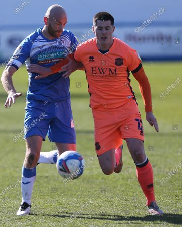 Jon Mellish of Carlisle United in action with Barrow's Jason Taylor   during the Sky Bet League 2 match between Barrow and Carlisle United at Holker Street, Barrow-in-Furness, England on 10th April 2021.