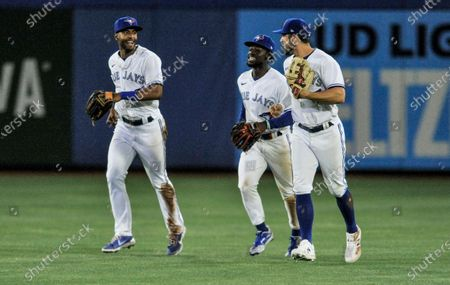 Toronto Blue Jays outfielders Josh Palacios, Jonathan Davis and Randal Grichuk, from left, head off the field after the team's 15-1 win over the Los Angeles Angels in a baseball game, early, in Dunedin, Fla