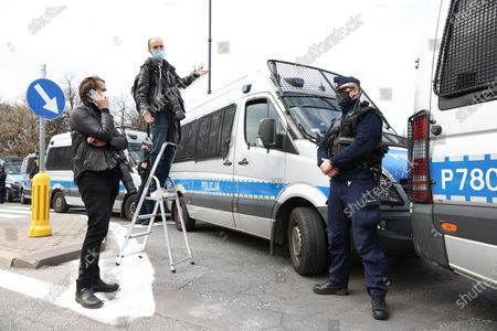 Stock Picture of A photographer gestures as police block access to the ceremony to be attended by president Andrzej Duda for the remembrance of the victims of the 2010 Smolensk air disaster in Warsaw, Poland on April 10, 2021. President Duda commemorated the 97 casualties of the Smolensk government plance crash from April 10, 2010 in which then president Lech Kaczynski also died. The ceremony on Saturday was cut off for all but state media and the vicinity of the ceremony had been hermetically sealed by police to ward off potential protesters. An investigation led by former minister of defence Antoni Macierewicz is said to conclude the 2010 Smolensk air crash was the result of an explosion despite official investigations having concluded the result of the crash came from human error leading to collision with a tree while flying a low altitude in low visibility circumstances.