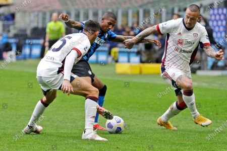 Stock Image of Inter Milan's Ashley Young, center, is challenged by Cagliari's Gabriele Zappa, left, and Cagliari's Radja Nainggolan, during a Serie A soccer match between Inter Milan and Cagliari at the San Siro stadium in Milan, Italy