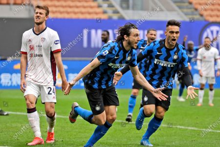 Inter Milan's Matteo Darmian, center, celebrates with teammate Inter Milan's Lautaro Martinez, right, after scoring the opening goal as Cagliari's Daniele Rugani reacts in dejection, left, during a Serie A soccer match between Inter Milan and Cagliari at the San Siro stadium in Milan, Italy