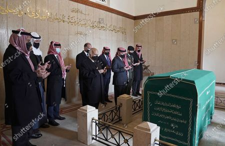 This photo from the Royal Court twitter account, shows Jordan's King Abdullah II, third right, Prince Hassan bin Talal, fifth right, Prince Hamzah bin Al Hussein, seventh right, and others pray during a visit to the tomb of the late King Abdullah I. King Abdullah II and his half brother Prince Hamzah have made their first joint public appearance since a palace feud last week. Members of the Jordanian royal family Sunday marked the centenary of the establishment of the Emirate of Transjordan, a British protectorate that preceded the kingdom