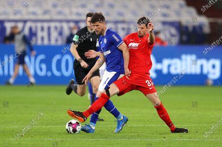 Klaas-Jan Huntelaar (L) of FC Schalke 04 is challenged by Tobias Strobl of FC Augsburg during the German Bundesliga soccer match between FC Schalke 04 and FC Augsburg at Veltins-Arena in Gelsenkirchen, Germany, 11 April 2021.