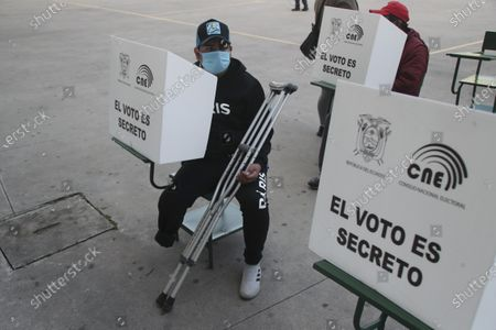 Man wearing a mask to curb the spread of COVID-19 waits for his turn to vote during a runoff presidential election in Quito, Ecuador, . Ecuadorians are voting Sunday to choose between Andres Arauz, from the Union of Hope coalition, an economist protégé of former President Rafael Correa, and former banker Guillermo Lasso, of Creating Opportunities party, or CREO