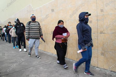 Voters wearing masks to curb the spread of the COVID-19 line up at a polling station during runoff presidential election in Quito, Ecuador, . Ecuadorians are voting to choose between Andres Arauz, from the Union of Hope coalition, an economist protégé of former President Rafael Correa, and former banker Guillermo Lasso, of Creating Opportunities party, or CREO