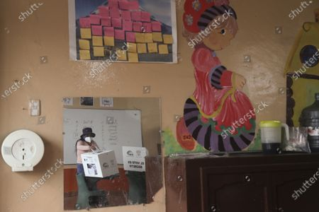 Woman casting her ballot is reflected at a mirror in at a school classroom during a runoff presidential election in Quito, Ecuador, . Ecuadorians are voting to choose between Andres Arauz, from the Union of Hope coalition, an economist protégé of former President Rafael Correa, and former banker Guillermo Lasso, of Creating Opportunities party, or CREO