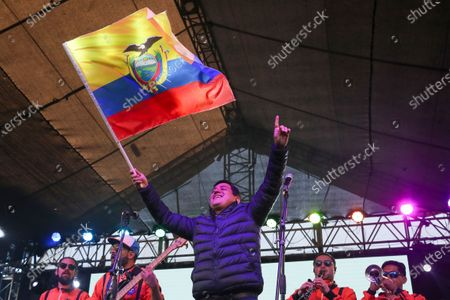 Andres Arauz, presidential candidate of the Alianza Union por la Esperanza, UNES, party waves an Ecuador national flag at his campaign headquarters in Quito, Ecuador, after the closing of the polls for a runoff presidential election . Ecuadorians voted Sunday to choose between Arauz, an economist protégé of former President Rafael Correa, and former banker Guillermo Lasso, of Creating Opportunities party, or CREO
