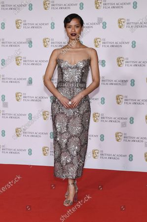 Actress Gugu Mbatha-Raw poses for photographers upon arrival at the Bafta Film Awards, in central London
