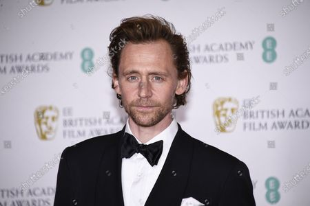 Actor Tom Hiddleston poses for photographers upon arrival at the Bafta Film Awards, in central London