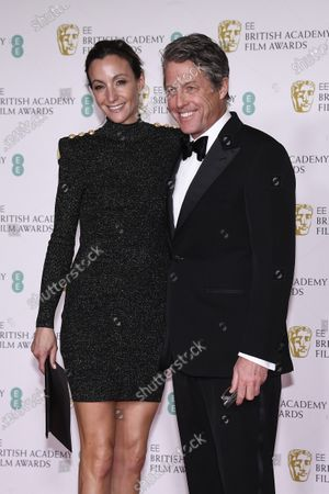 Actor Hugh Grant, right, and Anna Eberstein pose for photographers upon arrival at the Bafta Film Awards, in central London