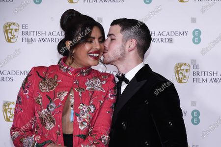 Actress Priyanka Chopra Jonas, left, is kissed by her husband singer Nick Jonas upon arrival at the Bafta Film Awards, in central London