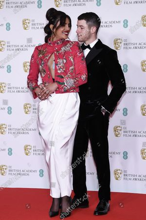 Actress Priyanka Chopra Jonas, left, and her husband singer Nick Jonas pose for photographers upon arrival at the Bafta Film Awards, in central London