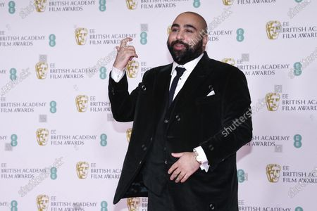Actor Asim Chaudhry poses for photographers upon arrival at the Bafta Film Awards, in central London