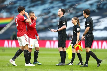 Referee Chris Kavanagh (C) and Manchester United's Harry Maguire (L) react during the English Premier League match between Tottenham Hotspur and Manchester United in London, Britain, 11 April 2021.