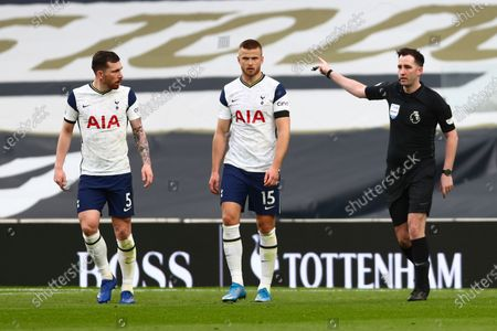 Tottenham's Pierre-Emile Hojbjerg, left and Tottenham's Eric Dier, walk past the referee during the English Premier League soccer match between Tottenham Hotspur and Manchester United at the Tottenham Hotspur Stadium in London